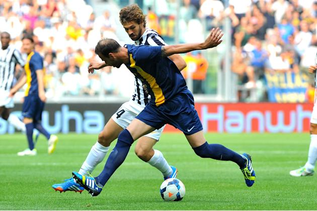 Juventus forward Fernando Llorente, of Spain, challenges for the ball with Hellas Verona defender Evangelos Moras, of Greece, during a Serie A soccer match between Juventus and Hellas Verona at the Ju