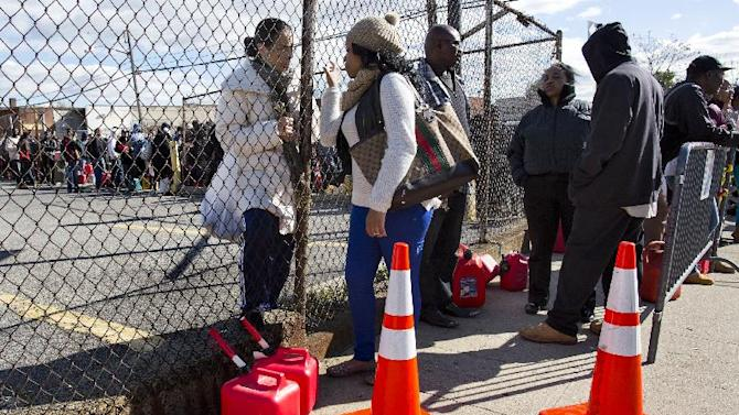 Jessica Martin, 28, center, of New York, the first person in line, talks to Maria Degano, of New York, behind fence, as they and others line up for free gas in the Jamaica neighborhood of the Queens borough of New York, Saturday, Nov. 3, 2012, in the wake of Superstorm Sandy. Trucks are being provided by the U.S. Department of Defense at the direction of President Barack Obama and are being deployed in coordination with the New York National Guard at the direction of the governor. (AP Photo/Craig Ruttle)