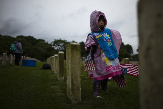 Viaenne Tom, 6, a girl scout, places a flag at a grave at Cypress Hills National Cemetery in Brooklyn, New York