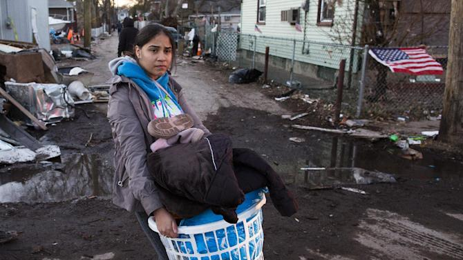 A resident of Staten Island's New Dorp Beach neighborhood carries a basket full of clothes and other items on her street that was devastated by Superstorm Sandy, Monday, Nov. 5, 2012, in New York. Although many areas of the metropolitan area are beginning to return to normal, neighborhoods of Staten Island's southern shore remain without power as the cleanup continues. (AP Photo/ John Minchillo)