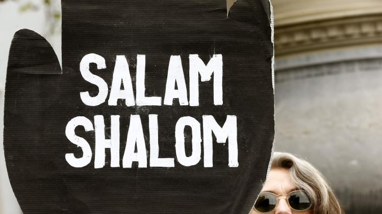 A woman displays poster demanding 'Salam, Shalom' during a demonstration for peace in Palestine in Zurich