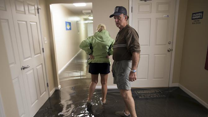 Chuck Richardson and his wife Ginger inspect their flooded Front Street office building in Georgetown