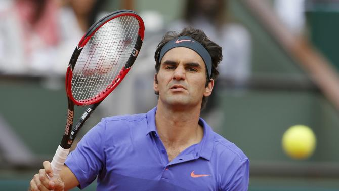Roger Federer of Switzerland plays a shot to Damir Dzumhur of Bosnia and Herzegovina during their men's singles match at the French Open tennis tournament at the Roland Garros stadium in Paris