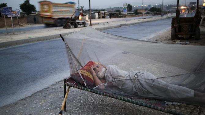 An elderly Pakistani man, who fled his home with his family from Pakistan's tribal areas, due to fighting between the Taliban and the army, sleeps on a bed covered with a mosquito net, on a roadside, on the outskirts of Islamabad, Pakistan, early Monday, May 20, 2013. As temperatures rise, many Pakistanis are sleeping outdoors to escape the heat trapped in their homes. (AP Photo/Muhammed Muheisen)