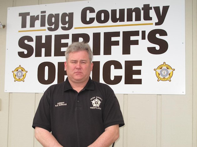 """In this Tuesday, Dec. 4, 2012, photo, Trigg County Sheriff Ray Burnam stands in front of the sheriff's department in Cadiz, Ky. When Burnam offered $1,000 of his own money as a reward for information leading to a conviction in three unsolved murder cases in western Kentucky county, law enforcement issued a court order demanding Burnam turn over his findings in one case and claimed he had gone """"rogue"""". AP Photo/Bruce Schreine"""