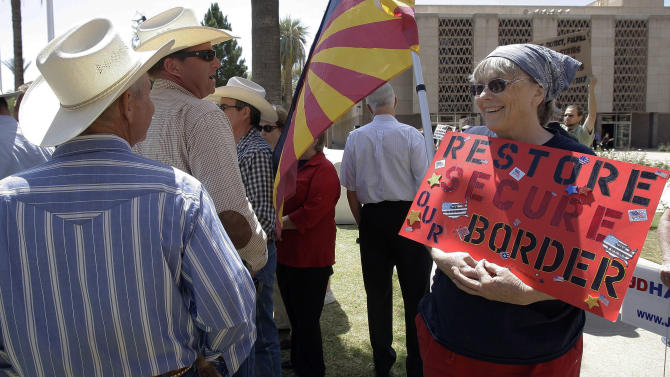 "FILE - In this April 13, 2010 file photo, Ginger Niesen, right, talks with ranchers John Ladd, left, and Ban Bell as they join other ranchers, state legislators and protestors at the Arizona Capitol in Phoenix following the shooting death of Arizona rancher Robert Krentz. Krentz was gunned down while checking water lines on his property near the border where ranchers scoff at the word ""secure."" (AP Photo/Ross D. Franklin)"