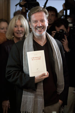 """Novelist Alexis Jenni, center, displays his book after he won the France's top literary prize, the Goncourt, with his book """"L'Art francais de la Guerre""""  """"The French Art of War"""", which deals with France's colonial wars in Algeria and Southeast Asia, in Paris, Wednesday, Nov. 2, 2011. As is traditional, the Prix Goncourt was announced at the Drouant restaurant in Paris. It comes with a euro 10 ($13) purse, but guarantees acclaim and significant sales for the winning author. (AP Photo/Thibaut Camus)"""
