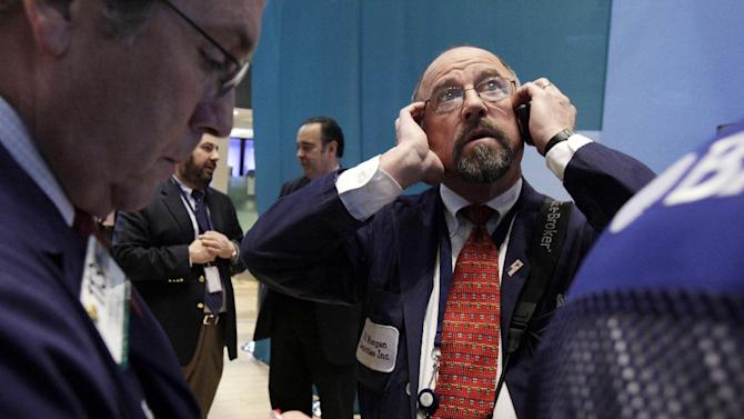 Trader Frederick Reimer, right, works on the floor of the New York Stock Exchange Tuesday, Dec. 11, 2012. Stocks opened higher Tuesday ahead of a meeting of the Federal Reserve and possible additional steps to bolster the U.S. economy.  (AP Photo/Richard Drew)