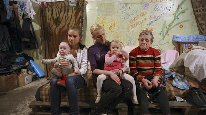 KIV33. Donetsk (Ukraine), 26/04/2015.- Women with children sit inside an air-raid shelter near the Chelyuskintsev coal mine in the Petrovsky district of Donetsk, Ukraine, 26 April 2015. Seven families with 13 children live at the shelter near the front line since October 2014. Russia on 23 April angrily rejected US accusations that it has deployed more air defence systems in Ukraine and accused Washington of sending military instructors to the country's conflict-torn east. US State Department spokeswoman Marie Harf had said earlier that the Russian military has deployed additional air defence systems into eastern Ukraine, resulting in the highest amount of such equipment in the conflict zone since August 2014. In addition, pro-Russian separatists continue to violate the terms of the Minsk agreement signed in February. (Rusia, Ucrania) EFE/EPA/NIKOLAI GONTAR