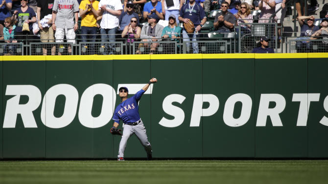 Texas Rangers right fielder Shin-Soo Choo throws the ball after fielding a double hit by Seattle Mariners' Robinson Cano during a baseball game, Sunday, April 19, 2015, in Seattle. (AP Photo/Ted S. Warren)
