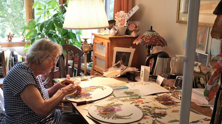 In this 2011 photo provided by the Fellowship Community, Norma Christie, a member of Fellowship Community works on a pressed flower project in her studio apartment on the grounds of the Fellowship, a nonprofit group in a commune-like setting north of New York City in Chestnut Ridge, N.Y. It takes an unusual approach to care of the elderly, and seeks to integrate aging residents with other members of the group, including co-workers and their children. (AP Photo/Fellowship Community, Miklos Gratzer)