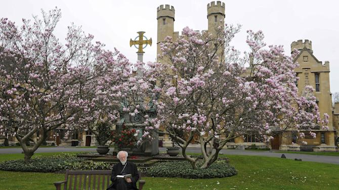 Archbishop of Canterbury Rowan Williams reads the Book of Common Prayer in the grounds of Lambeth Palace, London Friday March 16, 2012. Williams says he is stepping down at the end of the year, closing a tumultuous decade as leader of a global Anglican communion sharply divided on issues of sexuality and gender. He announced Friday that he will take up a new post as master of Magdalene College, Cambridge.    (AP Photo/Rebecca Naden/PA Wire)  UNITED KINGDOM OUT