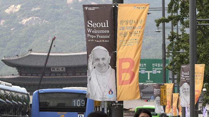People walk past banners welcoming Pope Francis on the street in Seoul, South Korea, Monday, Aug. 11, 2014. Pope Francis is scheduled to make a five-day trip to South Korea, starting Aug. 14 to participate in a Catholic youth festival and to preside over a beatification ceremony for 124 Korean martyrs. (AP Photo/Ahn Young-joon)