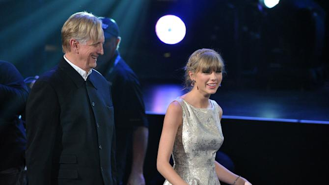 """T Bone Burnett, left, and Taylor Swift, right walk to the stage to accept the award for song written for visual media for """"Safe and Sound"""" (From The Hunger Games) at the 55th annual Grammy Awards on Sunday, Feb. 10, 2013, in Los Angeles. (Photo by John Shearer/Invision/AP)"""