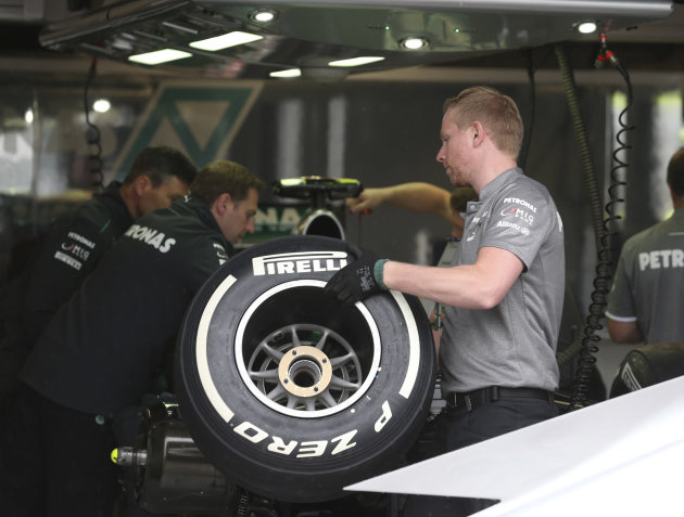 FILE- In this Thursday, June 6, 2013 file photo, a Mercedes mechanic holds a tire in the pit, at the Gilles Villeneuve racetrack, in Montreal, Canada. A tire testing session involving Mercedes and Pir