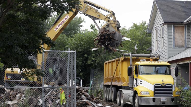 "Debris is loaded onto a truck at a house where three women were held captive and raped for more than a decade, Wednesday, Aug. 7, 2013, in Cleveland. Authorities want to make sure the rubble isn't sold online as ""murderabilia,"" though no one died there. The house was torn down as part of a deal that spared Ariel Castro a possible death sentence. He was sentenced last week to life in prison plus 1,000 years. He apologized but blamed his addiction to pornography. (AP Photo/Tony Dejak)"