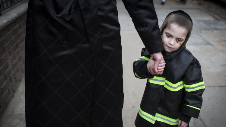 A child dressed as a fire fighter holds a man's hand during the Jewish holiday of Purim in the South Williamsburg suburb of New York