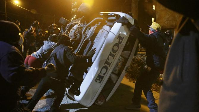 Protesters flip over a Ferguson police car in Ferguson