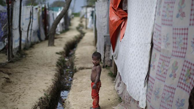A Pakistani Christian boy living in a slum, stands outside his home, on the outskirts of Islamabad, Pakistan, Monday, April 1, 2013. Slums which are built on illegal lands have neither running water or sewage disposal. (AP Photo/Muhammed Muheisen)