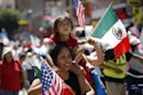 A child looks up as she rides among Mexican and American flags during the International Workers Day and Immigration Reform March on May Day in Los Angeles
