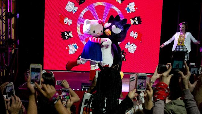 Fans take pictures of Hello Kitty and Bad Badtz-Maru at the Hello Kitty Con, the first-ever Hello Kitty fan convention, held at the Geffen Contemporary at MOCA Thursday, Oct. 30, 2014, in Los Angeles. The convention was held to honor the character's 40th birthday. (AP Photo/Jae C. Hong)