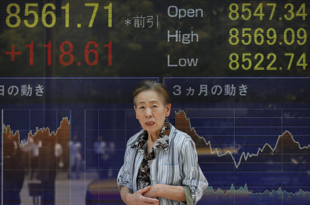 A woman walks in front of the electronic stock board of a securities firm showing Japan&#39;s Nikkei 225 index gained 118.61 points to 8561.71 in Tokyo, Friday, July 27, 2012. Asian stocks charged higher Friday after the European Central Bank&#39;s chief vowed to save the euro currency union from the continent&#39;s debt crisis and Samsung Electronics reported another record quarterly profit. (AP Photo/Itsuo Inouye)