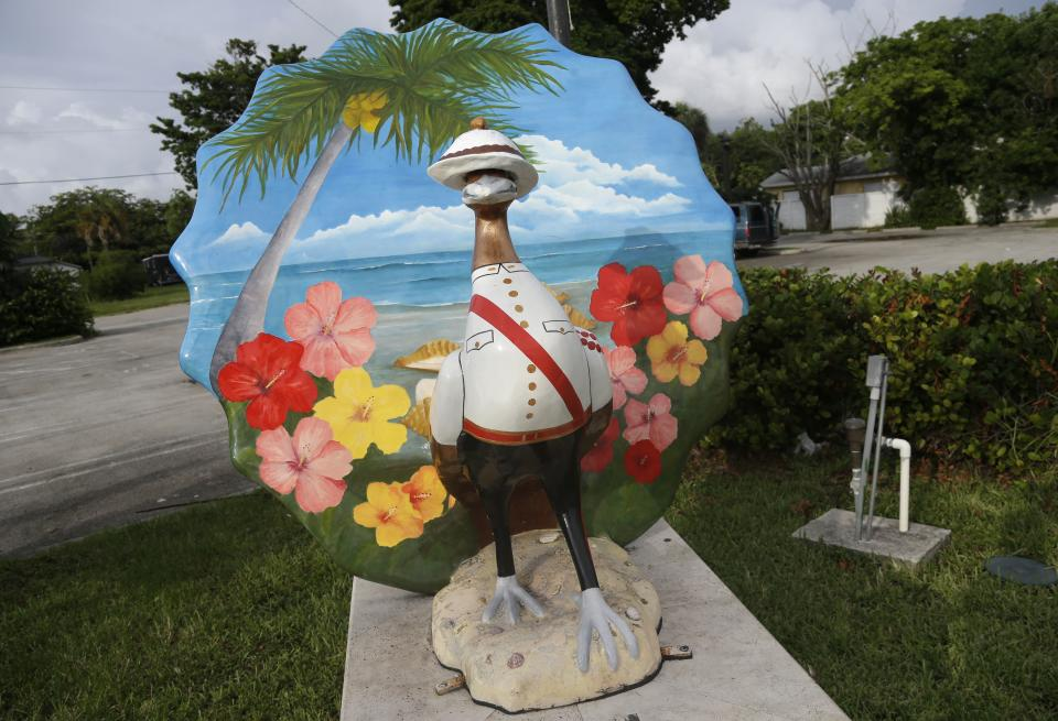 This Saturday, July 6, 2013 photo shows a sculpture of bird dressed as a Bahamian police officer in the heart of the business district in the Village West neighborhood of Coconut Grove in Miami. The community was settled by Bahamian immigrants in the 1880's. (AP Photo/Lynne Sladky)
