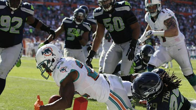Miami Dolphins running back Reggie Bush (22) stretches for a touchdown as Seattle Seahawks  Earl Thomas (29) attempts to tackle him during the first half of an NFL football game Sunday, Nov. 25, 2012 in Miami . (AP Photo/Gerry Broome)