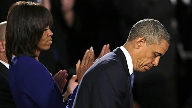 President Barack Obama, accompanied by first lady Michelle Obama. pauses after speaking at an interfaith healing service at the Cathedral of the Holy Cross in Boston, Thursday, April 18, 2013, for victims in Monday's Boston Marathon explosions. (AP Photo/Charles Krupa)