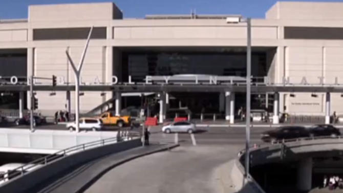 In this framegrabbed image from APTN the entrance to the Tom Bradley International Terminal in Los Angeles can be seen Tuesday Oct. 15, 2013. A baggage handler was arrested Tuesday in connection with dry ice explosions Sunday and Monday at Los Angeles International Airport after police stepped up patrols and increased its checks on employees. Dicarlo Bennett, a 28-year-old employee for the ground handling company Servisair, was booked for possession of a destructive device near an aircraft. (AP Photo\APTN)