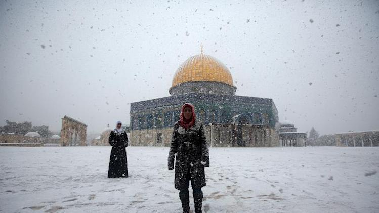 Two Palestinian women stand in front of the Dome of the Rock at the Al-Aqsa mosques compound during snowfall in Jerusalem on December 12, 2013