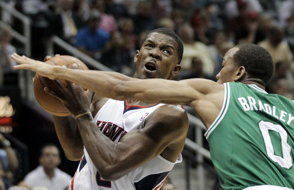 Atlanta Hawks' Joe Johnson, left, handles the ball in front of Boston Celtics' Avery Bradley during the second quarter of Game 1 of an opening-round NBA basketball playoff series, Sunday, April 29, 2012, in Atlanta. (AP Photo/David Goldman)