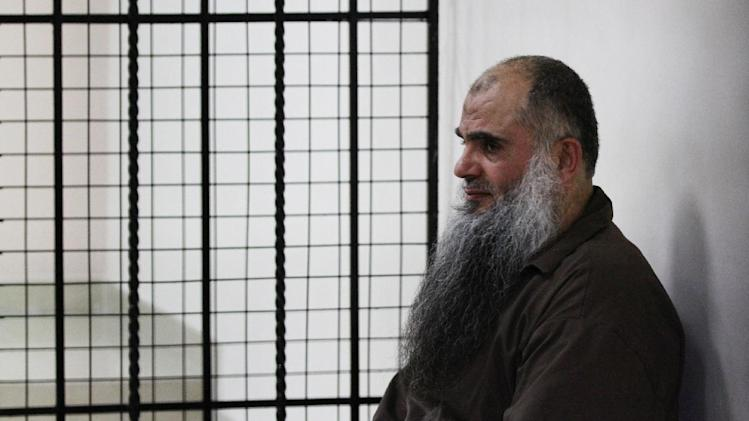 The radical al-Qaida-linked preacher Abu Qatada sits behind bars at the Jordanian military court in Amman, Jordan, Thursday, June 26, 2014. A Jordanian military court on Thursday acquitted Abu Qatada of terrorism charges over a foiled 1999 plot to attack an American school in the Jordanian capital, Amman. (AP Photo/Raad Adayleh)