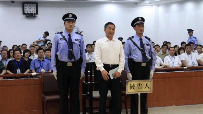 In this photo released by the Jinan Intermediate People's Court, Bo Xilai, center, who was tried last month on charges of taking bribes, embezzlement and abuse of power, stands inside the court in Jinan, in eastern China's Shandong province, Sunday, Sept. 22, 2013. The Chinese court convicted the fallen politician of corruption and sentenced him to life in prison. (AP Photo/Jinan Intermediate People's Court)