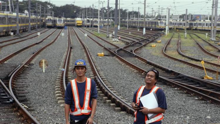Workers inspect tracks on a railway at a depot of Southeast Asia's first light rail transit network, which is 29-years-old, in Manila