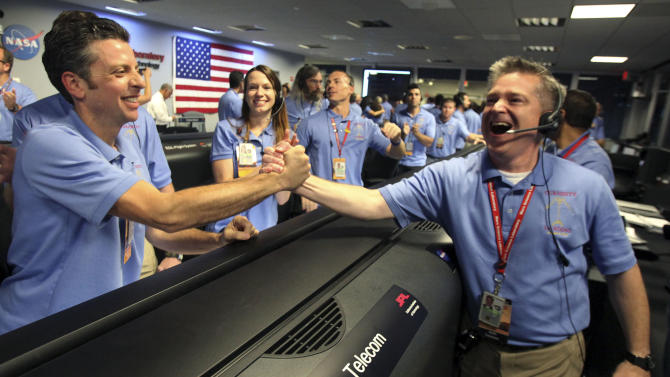 Flight director Keith Comeaux, right, celebrates with Martin Greco after a successful landing inside the Spaceflight Operations Facility for NASA's Mars Science Laboratory Curiosity rover at Jet Propulsion Laboratory  in Pasadena, Calif., Sunday, Aug. 5, 2012. The Curiosity robot is equipped with a nuclear-powered lab capable of vaporizing rocks and ingesting soil, measuring habitability, and potentially paving the way for human exploration. (AP Photo/Brian van der Brug,Pool)