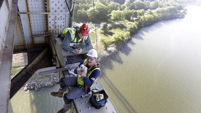 Wildlife biologist Chris Nadareski, foreground, of the New York City Department of Environmental Protection, assisted by Port Authority structural specialist Pete Mizialko, holds one of four peregrine falcon chicks for banding, at a nest at the east tower of the George Washington Bridge, over the Hudson River, in New York, Tuesday, May 21, 2013. The chicks hatched three weeks ago on a girder six feet below the bridge's lower level. Their parents are among 20 pairs of peregrine falcons living in New York City. (AP Photo/Richard Drew)
