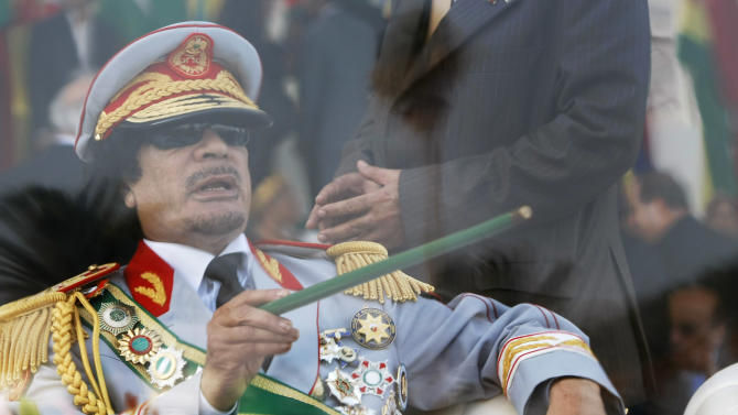 FILE - In this Tuesday, Sept. 1, 2009 file photo, Libyan leader Moammar Gadhafi gestures with a green cane as he takes his seat behind bulletproof glass for a military parade in Green Square, Tripoli, Libya. Libyan special forces stormed a two-day-old protest encampment in the country's second largest city of Benghazi, clearing the area early Saturday, Feb. 19, 2011, said witnesses, as a human rights group estimate scores of people have died in the harsh crackdown on days of demonstrations. (AP Photo/Ben Curtis, File)