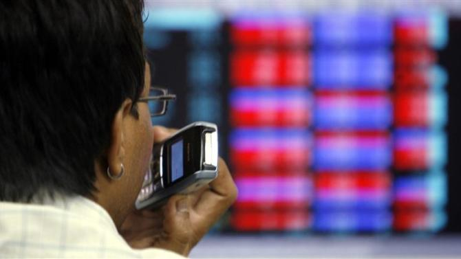 A stockbroker speaks on his mobile phone as he looks at a terminal while trading at a stock brokerage firm in Mumbai