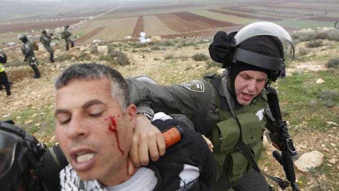 Israeli border policeman detains a Palestinian protester during clashes following a demonstration against Israeli settlements in the West Bank village of Turmus Aya, near Ramallah