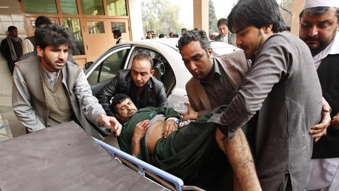 Afghan men carry a wounded man at a hospital in Jalalabad