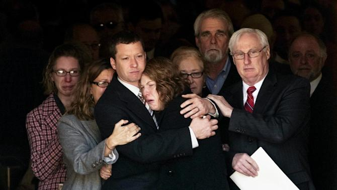 Jason Derkosh holds his wife, Elizabeth, at the funeral of their 2-year-old son, Maddox, at Saint Bernard Church in Mount Lebanon, Pa., on Friday, Nov. 9, 2012. Maddox Derkosh was killed Sunday after he fell from a wooden railing overlooking the painted dogs exhibit at the Pittsburgh Zoo and PPG Aquarium and bled to death after being mauled by the dogs.  (AP Photo/Tribune Review, Justin Merriman)  PITTSBURGH OUT