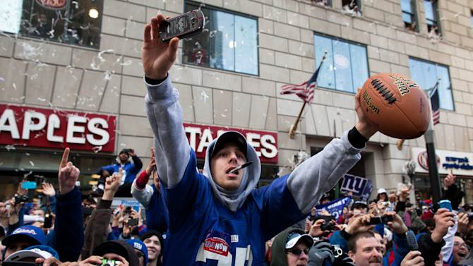New York Giants fans cheer and reach for autographs from the players during the team's NFL football Super Bowl parade in New York, Tuesday, Feb. 7, 2012. The Giants returned from their Super Bowl win to a celebration the likes that only New York can throw: a ticker-tape parade in the Canyon of Heroes on Broadway, where the city has honored stars for almost a century. (AP Photo/John Minchillo)