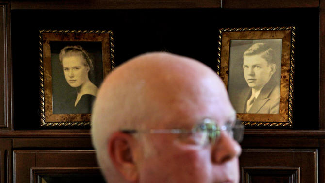 In this May 17, 2012 photo, framed photos of Tom and Charlotte Little sit in a bookcase in the home of their son Tom Little Jr., foreground, in Roswell, Ga. Little was 12 when his parents were killed aboard a chartered Air France plane carrying a group of Atlanta's cultural leaders that crashed on takeoff at Orly Field in Paris fifty years ago. (AP Photo/David Goldman)