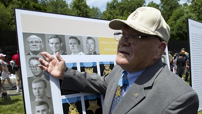 Medal of Honor recipient Bennie Adkins gestures towards his picture as part of the unveiling of the Limited Edition of Honor: Vietnam War Forever Stamps during a Memorial Day observance ceremony, Monday, May 25, 2015, at the Vietnam Veterans Memorial in Washington. (AP Photo/Jose Luis Magana)