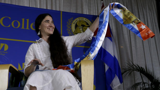 Blogger and activist Yoani Sanchez, of Cuba, holds up a gift given to her in the colors of the Cuban flag before speaking at the Freedom Tower of Miami Dade College, Monday, April 1, 2013, in Miami. Sanchez has gained thousands of followers worldwide for her candid descriptions of modern life in Cuba on her blog Generation Y. (AP Photo/Lynne Sladky)