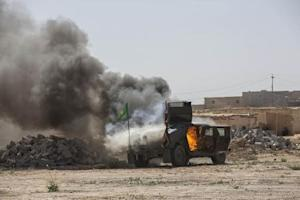 A military vehicle, belonging to Shi'ite fighters known as Hashid Shaabi, burns after being hit by Islamic State militants, during clashes in northern Tikrit