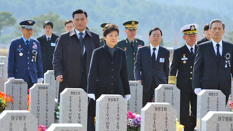 South Korean President Park Geun-hye, center, walks through gravestones for South Korean sailors killed in a sunken war ship, at a cemetery in Daejeon, South Korea, Tuesday, March 26, 2013. An explosion ripped apart the 1,200-ton warship, killing 46 sailors near the maritime border with North Korea in 2010. South Korea marks three years from the incident on March 26. (AP Photo/Kim Jae-hwan, Pool)