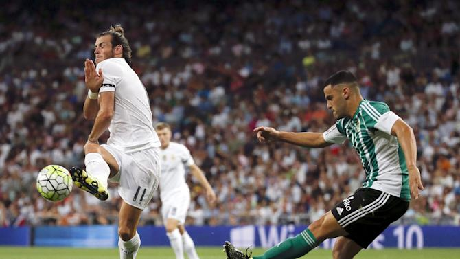 Real Madrid's Bale protects himself from a kick by Real Betis' Van der Vaart during their Spanish first division soccer match at Santiago Bernabeu stadium in Madrid, Spain