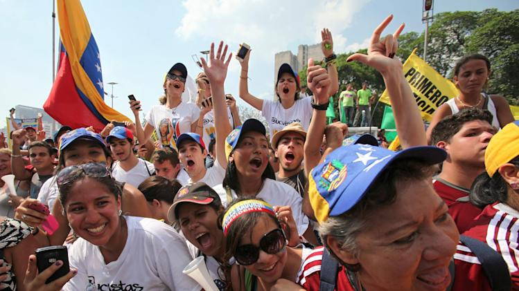 FILE - In this April 7, 2013 file photo, supporters of opposition presidential candidate Henrique Capriles cheer holding up their cell phones at a campaign rally along Bolivar Avenue in Caracas, Venezuela. Tinedo Guia, president of Venezuela's largest journalists association, said the government does not appear to fully grasp that people distrustful of state-controlled media can increasingly rely on Internet-driven grassroots reporting. Mobile phone subscriptions more than doubled from 47 to 98 percent between 2005 and 2010, and the number of mobile broadband subscriptions grew from less than 1 percent to more than a quarter of the population over the same period. (AP Photo/Fernando Llano, File)